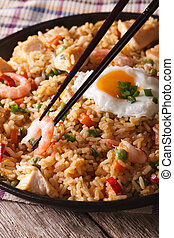 Fried rice nasi goreng with chicken and shrimp close-up...