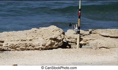 fishing rod on the shore and the yacht at sea