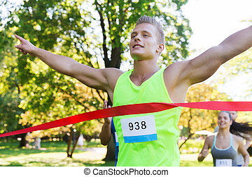 happy young male runner winning on race finish - fitness,...