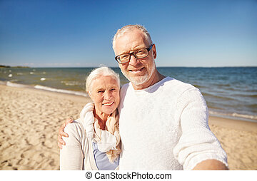 seniors taking picture with selfie stick on beach - age,...