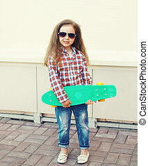 Fashion little girl child with skateboard in the city