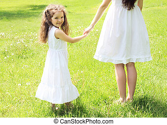 Happy child holding hands mother walking in sunny summer meadow