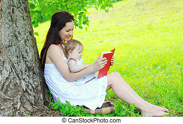 Mother and child reading book together under tree in summer...