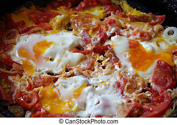 Fried eggs with tomatoes and onions in a pig-iron frying pan...