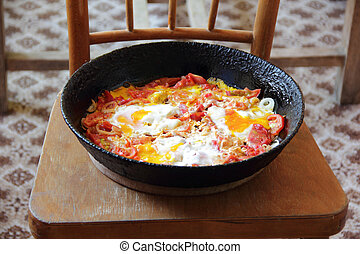 Fried eggs with tomatoes in a pig-iron frying pan - Fried...