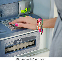 Close-up of hand entering PIN/pass code on ATM/bank machine...