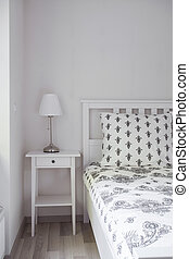 Wooden nightstand and bed - Image of white wooden nightstand...
