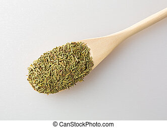 Dried rosemary leaves in spoon on a cutting board