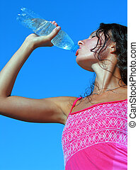 Young woman drinking cold water in hot day - Thirst. Young...