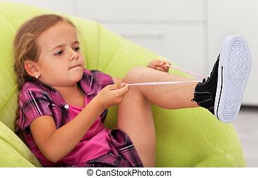 The struggle - cute little girl ties shoe