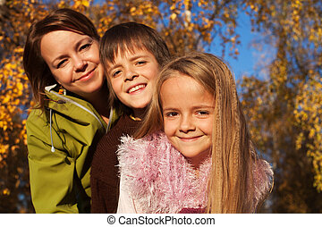 Autumn family portrait in the sunny forest