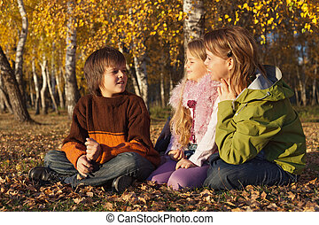 Family relaxing in the sunny autumn forest