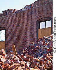 A demolition site with a pile of demolished brick wall and...