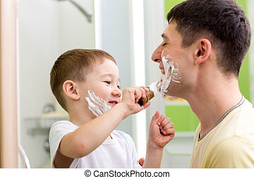 Father and his child son shaving and having fun in bathroom...