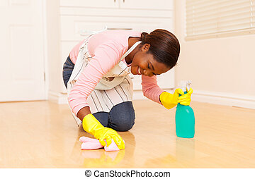 young african woman wiping wooden floor - happy young...