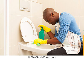 african american man cleaning toilet at home