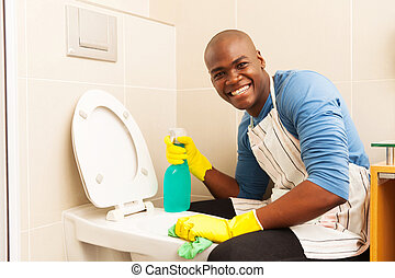 african man cleaning toilet - portrait of happy african man...