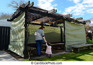 Jewish woman and child visiting their family Sukkah in the...