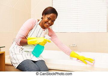 young african woman cleaning bathtub