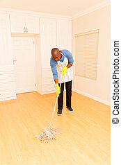 young african man mopping the floor in his empty apartment