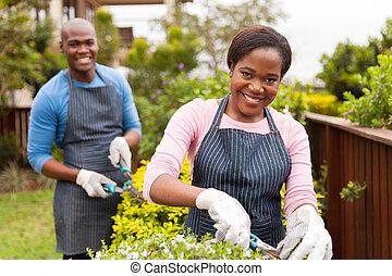 young black couple working together in home garden -...