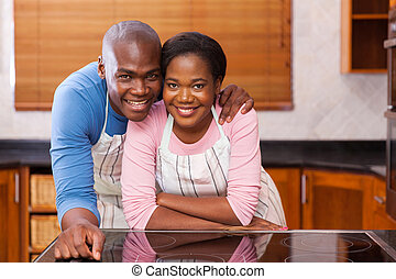african couple leaning against the kitchen counter -...