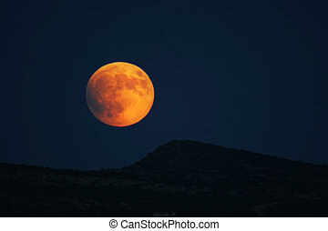 Super Moon Rising - Super moon rising over hills prior to...