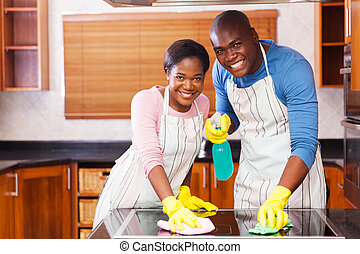 young african american couple cleaning kitchen - young...