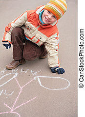 Boy drawing by chalk on asphalt