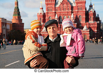 Grandfather with grandson and granddauther on red square