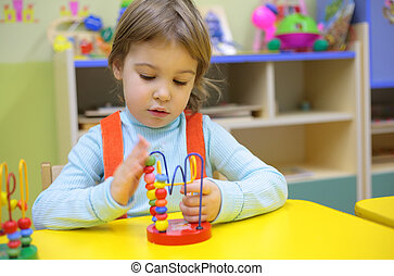 Little girl plays in kindergarten
