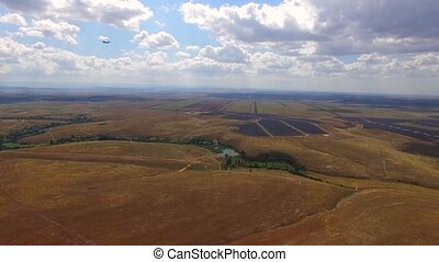 Passenger Plane Flying Over Rural Fields And Landing -...