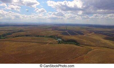 Passenger Plane Flying Over Rural Fields And Landing -...