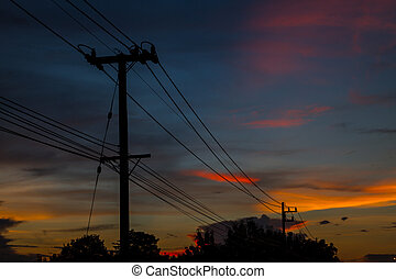 silhouette of electric post and wires in the background of...