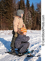 Two boys with snow scooter