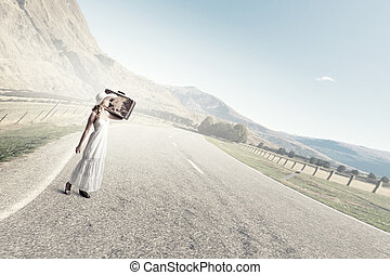 She is traveling light - Woman with suitcase in white long...