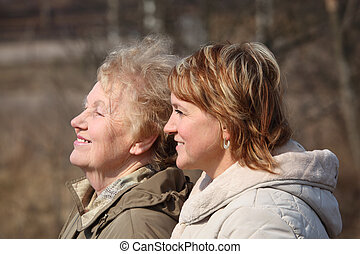 Smiling elderly woman and her daughter in profile