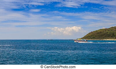 motorboat outruns large boat against island and boundless...