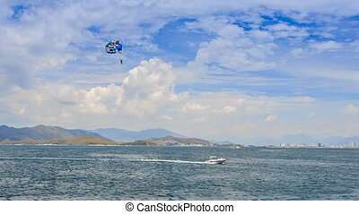 parasailing over azure sea boat makes tight turn against...