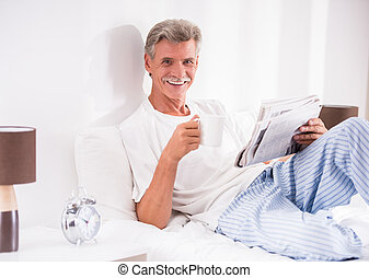 Senior man with a cup of coffee is reading newspaper in bed