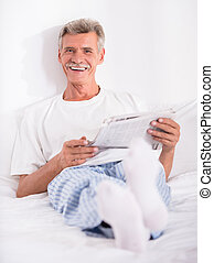 Senior man is reading newspaper in bed and looking at the...