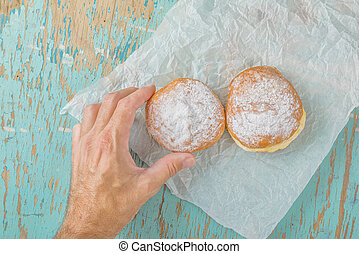 Hand reaches for sweet sugary donut on rustic table - Male...