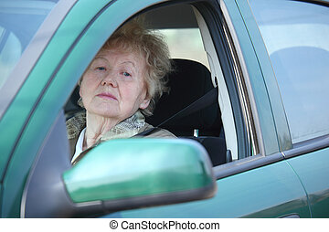 Elderly woman looks in car`s window