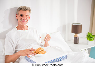 Senior man - Happy senior man is having breakfast in bed.