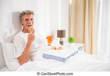 Senior man - Happy senior man is having breakfast in bed