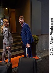 business people couple entering hotel - Young business...