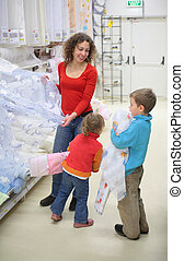 Young woman with children in shop of textile