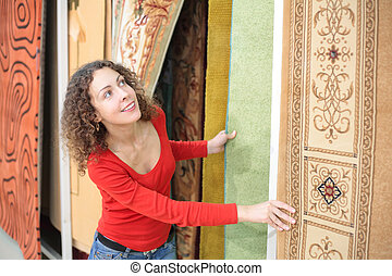 Young woman in shop with carpets