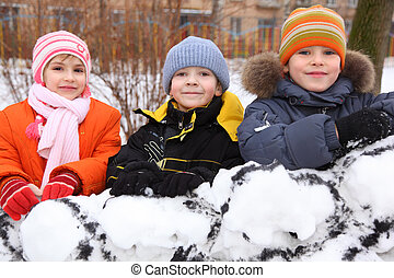 Three children on wall of snow fortress in court yard