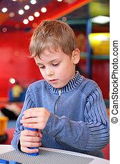 boy plays with plastic constructor in kindergarten